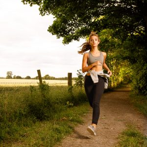 A young woman runs along a canal path, lit with flash - photo: Brian Worley