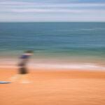 Young Surfer Dragging His Board © Chenx Ni